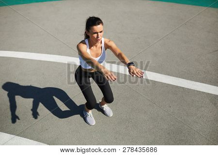 Serious concentrated young woman with wristwatch breathing out air and doing squat at stadium