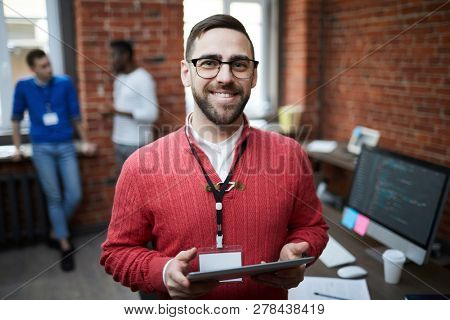 Young successful engineering office staff with touchpad standing in front of camera while networking