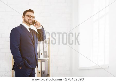 Executive Worker Talking On Phone In Office, Standing Near Window, Copy Space