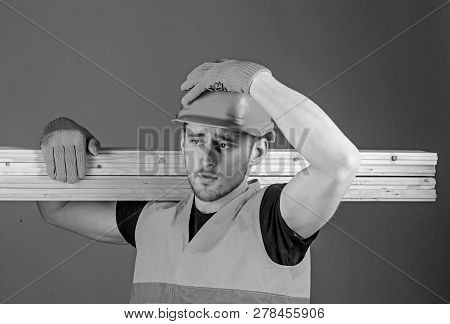 Safety And Protection Concept. Carpenter, Woodworker, Strong Builder On Serious Face Carries Wooden