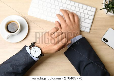 Businessman With Wrist Watch Working At Office Table, Closeup. Time Management