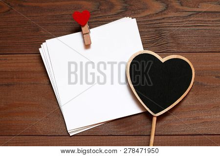 Pile Of Cards With Wooden Clothespin With Red Heart And Chalkboard Black Wooden Heart On The Wooden
