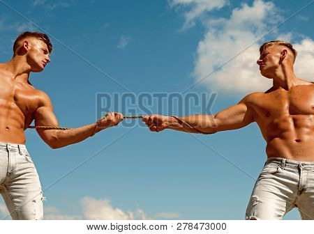 Feeling Power. Strong Men Pull Rope With Muscular Hand Strength. Men Shows Off Their Strength Agains