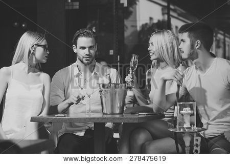 Twins Women And Men Relax In Shisha Cafe Outdoor. Friends Vapor Hookah And Drink Alcohol In Bar Loun