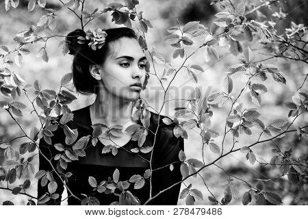 Girl With Flower In Brunette Hair, Hairstyle Posing In Green Tree Leaves In Spring Forest On Idyllic