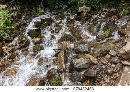 Fast Mountain Stream With Stones, Surrounded By Greenery. Cascade Of Small Waterfalls In A Mountain