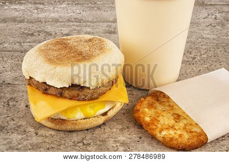 Breakfast Sandwich With Coffee And Hash Brown On Concrete Table. English Muffin, Egg, Cheese And Sau