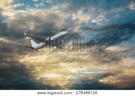 The Passenger Plane Flies Over The Clouds During Sunset View Of Passenger Long Range Aircraft.