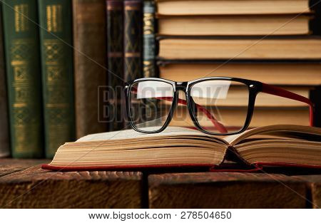 Education Learning Concept With Opened Book And Glasses In Old L