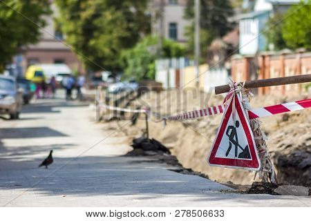 Construction Roadwork On Street In City. Red Safety Sign Warns About Roadworks. Be Careful, Danger O