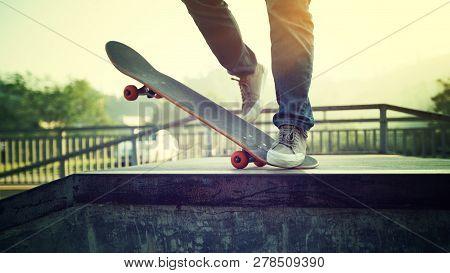 Woman Young Skateboarder Skateboarding At Skatepark Ramp