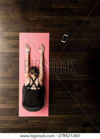 Woman Doing Yoga In Class On Mat View From Above