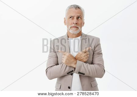 Unsure Hesitant And Questioned Old Businessman In Grey Suit With Grey Beard And Hair Crossing Hands