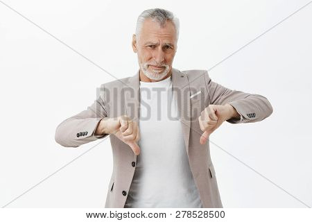 Portrait Of Unimpressed Old Businessman With Beard And Grey Hair In Elegant Suit Showing Thumbs Down
