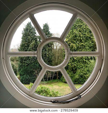 Circular port hole window view into garden