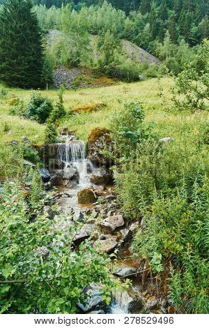 Small brook with waterfall in nature in France
