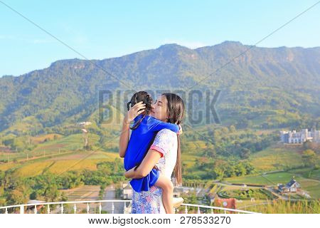 Asian Mom Cuddle Her Daughter With Love On Balcony At Hillside.