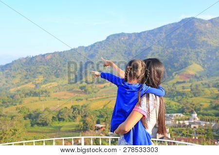 Rear View Asian Mother Carrying Daughter On Balcony At Hillside And Pointing Out That To See.