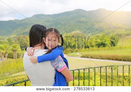 Asian Mother Carrying Daughter On Balcony At Hillside With Looking Camera.
