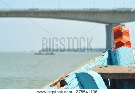 The Prow Of A Vietnamese Wooden Boat Is Brightly Coloured In Blue And Orange. In The Distance Is A L
