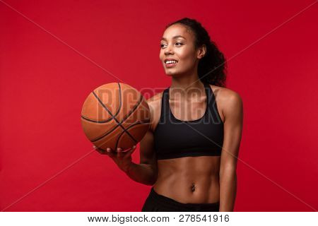 Image of a strong young african sports fitness woman basketball player posing isolated over red wall background holding ball.