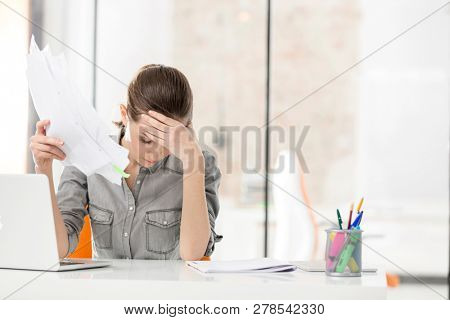 Overworked businesswoman holding documents while suffering from headache