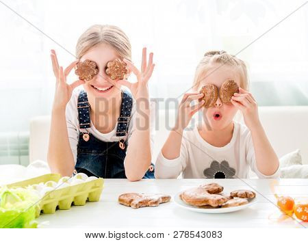 Happy little girls sitting at the kitchen table and holding Easter cookies in front of their eyes