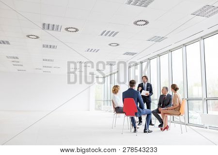 Businessman discussing with colleagues against window in new office during meeting