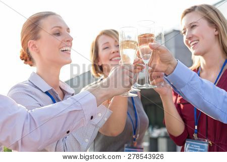 Smiling business colleagues holding sparklers during party on rooftop