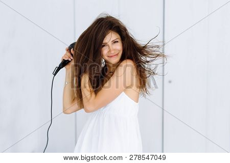 Woman In Bathrobe Drying Her Hair With Dryer Over White Background