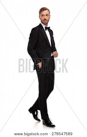 elegant businessman steps to side with hand in pockets on white background and looks to side, full body picture