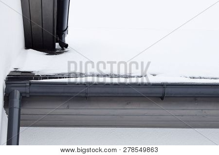 Dark grey plastic rain gutter with drain downspout pipe installed on asphalt shingles roof covered with white snow and wooden eaves with copy space for text on snowy roof at winter day. poster