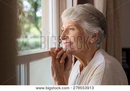 Happy senior woman standing at window and looking outside. Beautiful grandmother smiling while looking through the window. Cheerful old woman relaxing in home while standing at window sill. poster