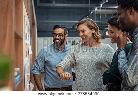 Group of mature businesspeople planning business strategy while looking at infographic on wall. Business men and casual women looking at pie charts. Successful startup partners feeling happy.