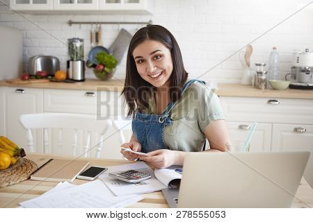 Happy Attractive Young Woman Sitting At Kitchen Table Working Through Papers, Calculating Home Budge