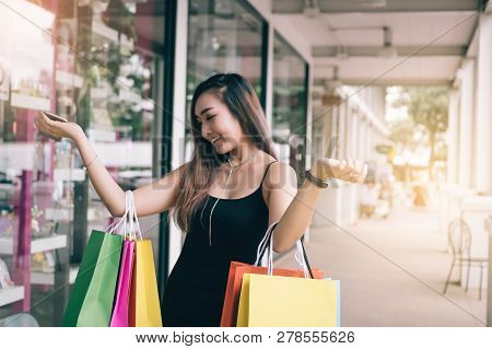 Enjoying Of Asian Young Woman Shopping In The Outlet Mall With Carrying Paper Bags.