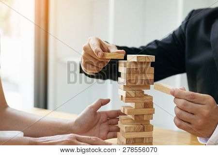 Two Businessmen Help To Hold The Wood Block To Fall Down.