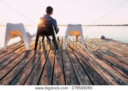 Men Is Relaxing And Meditation On Chair At Footbridge On Lake. Concept Of Waiting For Summer.