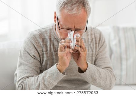 healthcare, flu, hygiene and people concept - sick senior man with paper wipe blowing his nose at home