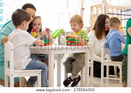 Preschool Teacher With Kids Playing With Colorful Wooden Educational Toys At Kindergarten
