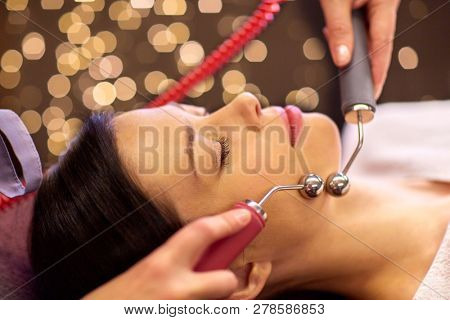 people, beauty, cosmetology and technology concept - beautiful young woman having needle free mesotherapy or hydradermie facial treatment by microcurrent firming device in spa poster