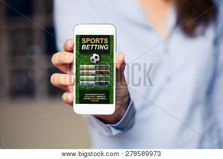 Sports Betting Website In A Mobile Phone Screen While Woman Holds The Device.