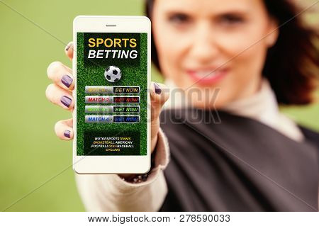 Woman Showing Mobile Phone With Sports Betting Website In The Screen.