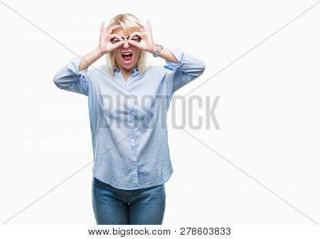 Young beautiful blonde business woman wearing glasses over isolated background doing ok gesture like binoculars sticking tongue out, eyes looking through fingers. Crazy expression.