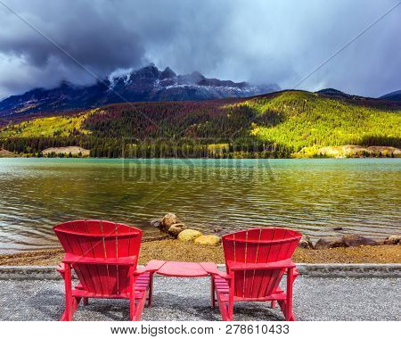 Comfortable red deck chairs stand over the lake. Thunderclouds swirl in the sky. Scenic autumn in the Rockies of Canada. Concept of ecological, active and photo-tourism