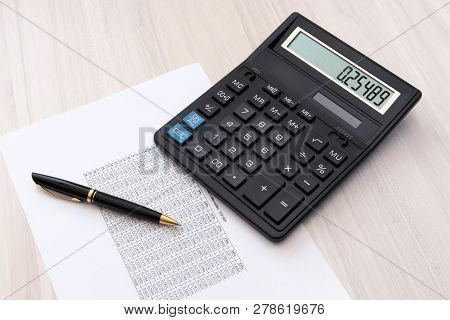 Calculator, Pen And Sheet Of Paper With Spreadsheet  On The Table