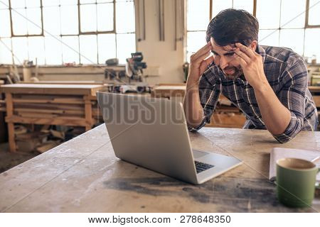Stressed Out Woodworker Using A Laptop In His Carpentry Studio