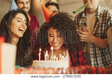 Excited Girl Ready To Blow Out Candles On Cake On Birthday Party With Happy Friends. Happy Birthday