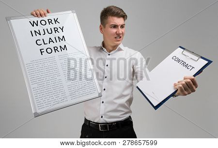 Young Man Holding A Form With A Claim Of Injury At Work And Blank Contract Form Isolated On A Light