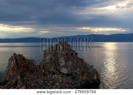 Dusk Landscape With Shaman Rock Or Cape Burkhan At The Olkhon Island On Baikal Lake. Summer Vacation